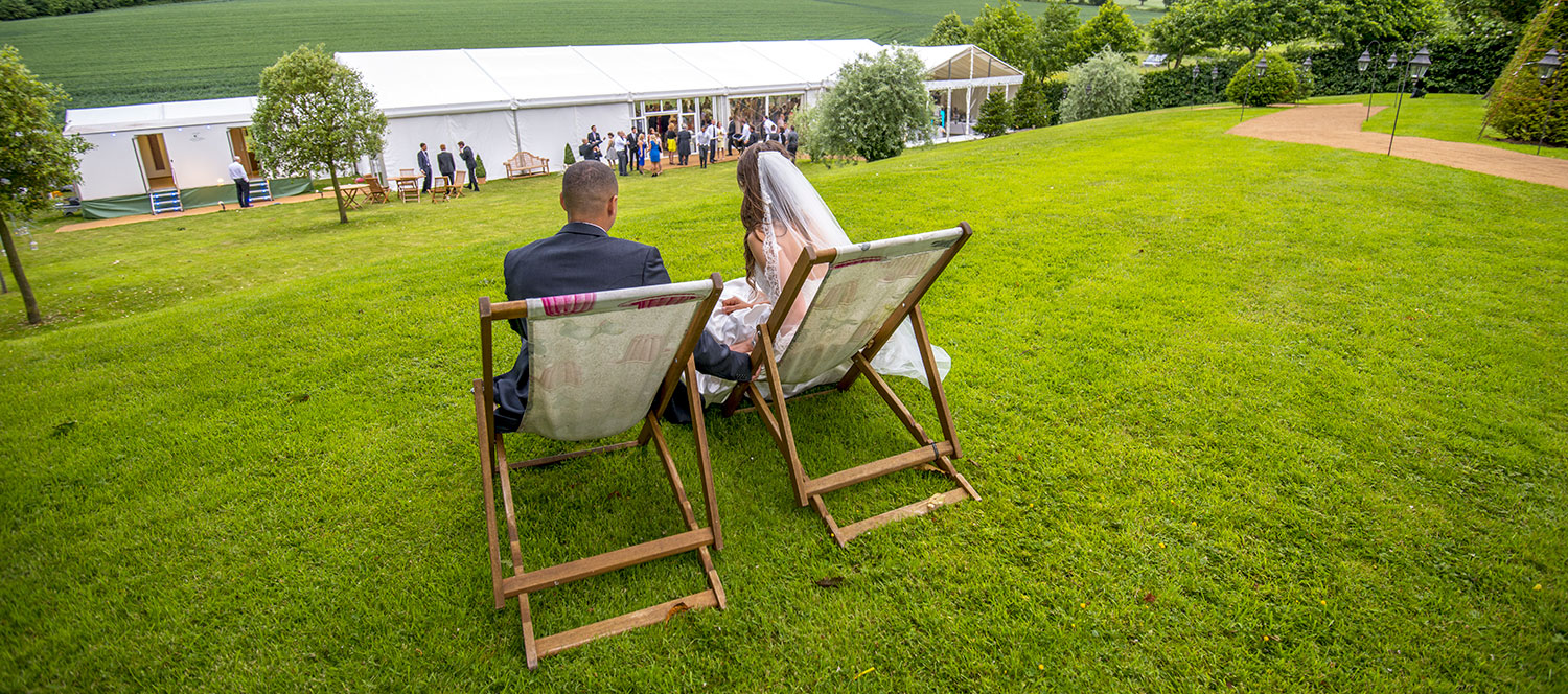 Wedding Marquee with Bride & Groom on Deck Chairs