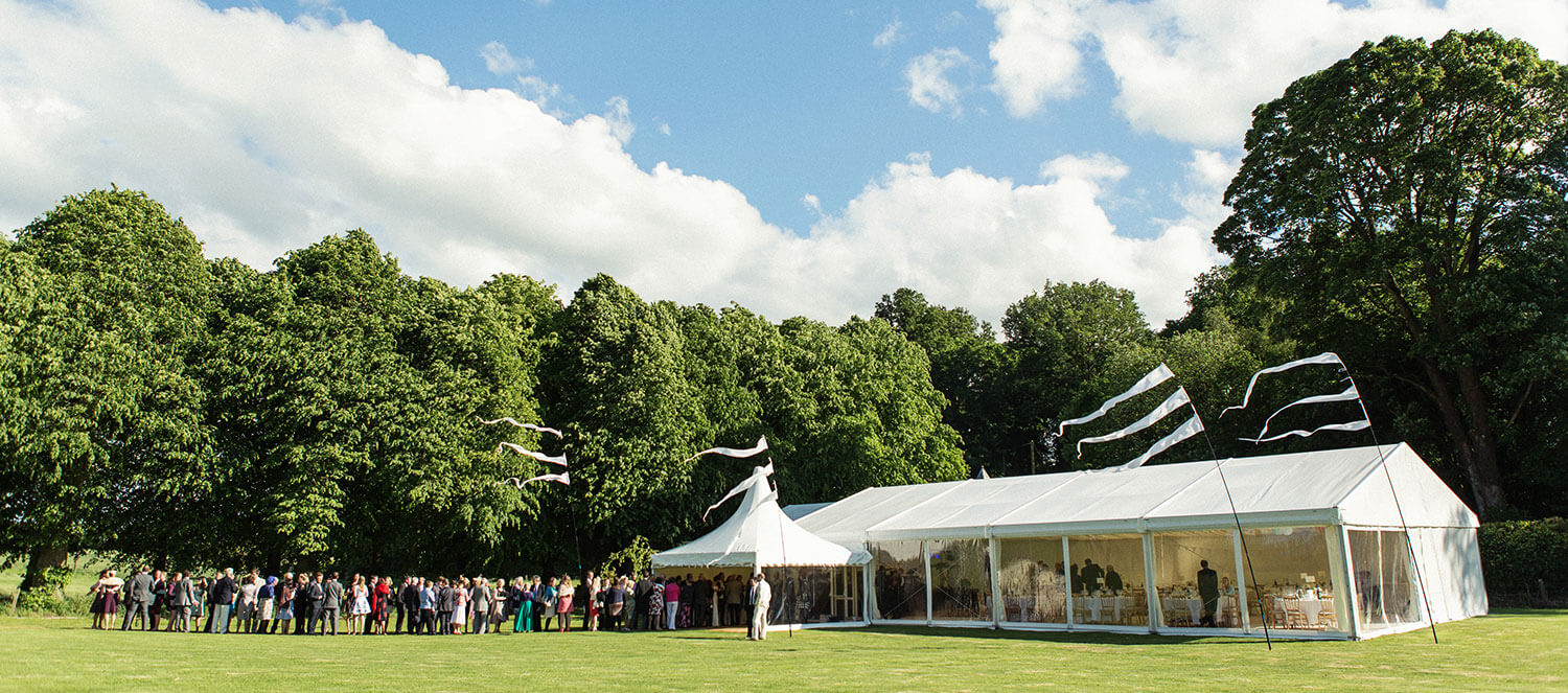 Guests having fun around tables and chairs in a marquee in the grounds of a mansion size property