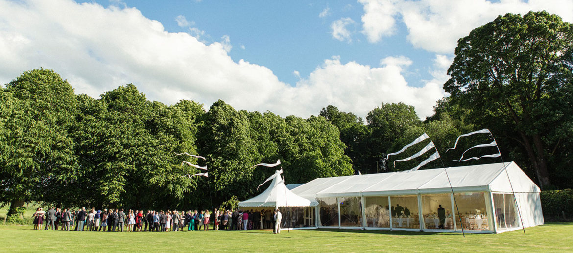 Wedding guests standing outside of the marquee